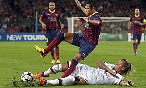 Barcelona's Alexis Sanchez is tackled by AC Milan's Philippe Mexes