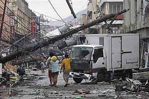 Survivors walk under a fallen electric post after super Typhoon Haiyan battered Tacloban city